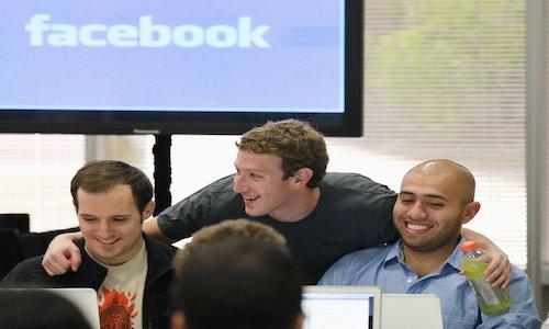 Mark Zuckerberg standing behind two colleagues.
